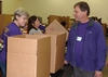 Mitch Baker '76 waits to transfer a 40 lb. box of food packed by hard-working Colorado Knox Club volunteers, Ann Petrila P'12 and Georgine Kryda '83.