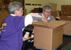 Linda Pohle '69 and Gina Frank P'05 fill a box that contributed to the nearly 4 tons of food that was packed during the 2 1/2 hours.